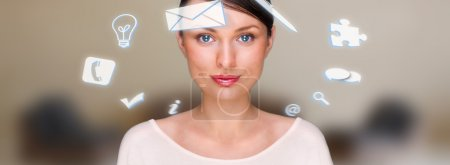 Photo for A business woman with icons of her affairs floating around her head. Portrait of pretty girl working with her virtual pc looking at camera and smiling. Daily de - Royalty Free Image
