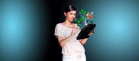 Photo pour Portrait d'affiche de belle jeune femme tenant son dispositif universel - tablet pc. beaucoup de choses font leur apparition de l'écran. universalité des appareils modernes - image libre de droit