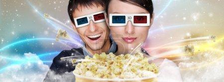 Photo pour Portrait de jeune couple moderne élégant, lunettes 3d, je regarde le film en 3d à la maison embrasser et manger des pop corn qui explose. - image libre de droit