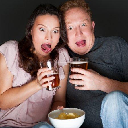 Photo pour Un couple qui regarde un film d'horreur et ça leur fait tellement peur qu'ils crient . - image libre de droit