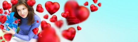Delighted woman opening a gift sitting on the bean bag at home and beautiful red heart shapes are flying around. Valentine day concept poster