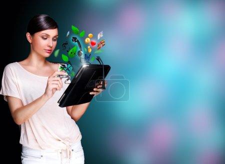 Photo pour Portrait d'affiche de belle jeune femme tenant son dispositif universel - tablet pc. beaucoup de choses font leur apparition de l'écran. universalité du concept de dispositifs modernes - image libre de droit