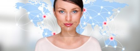 Portrait of young woman standing in front of big world map and looking at camera. Server locations and actual online connections are displayed on virtual map. Hosting provider concept