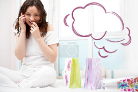 Portrait of young beautiful awake woman with gifts on bed at bedroom. Talking with her boyfriend by mobile phone. Cloud balloon overhead