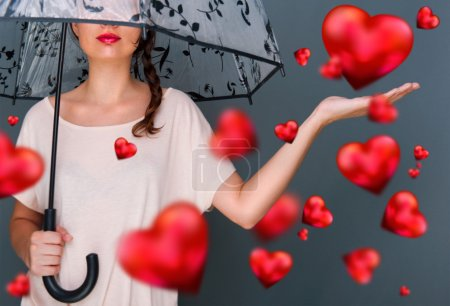 Young fashionable woman holding umbrella standing against grey background red hearts are floating around her. Love rain concept