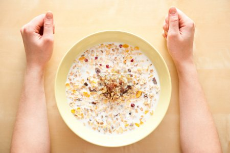 Photo for Cereal muesli breakfast with dried fruit and nuts and milk and woman hands on table. Top View - Royalty Free Image