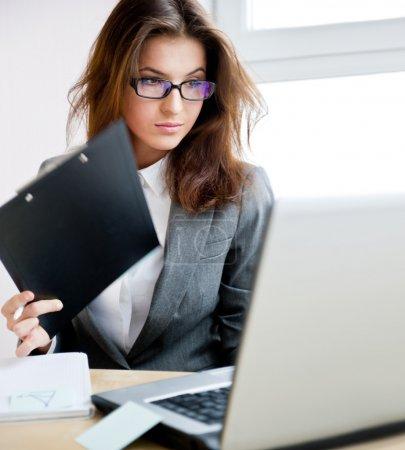 Photo pour Adulte jeune jolie femme d'affaires travaillant à son bureau. elle est très occupée et chaud. - image libre de droit