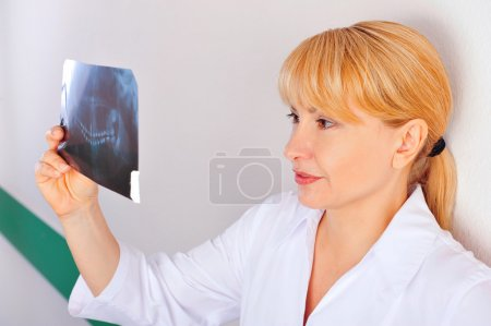Portrait of smiling caucasian woman doctor wearing uniform standing against wall at hospital looking at xray results of her patient