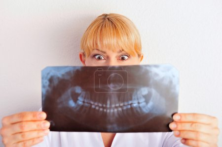 Portrait of funny smiling caucasian woman doctor wearing uniform standing against wall at hospital looking at xray results of her patient and she is very surprised