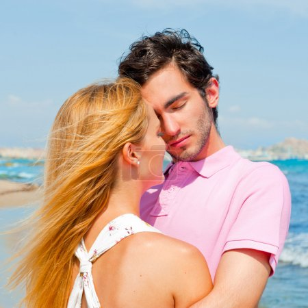 Photo for Portrait of young couple in love embracing at beach and enjoying time being together - Royalty Free Image