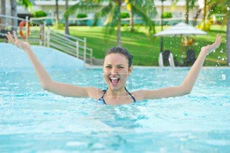 Woman in a pool having fun with splash