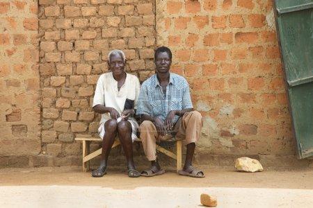 Foto de Lira, Ouganda - 9 juin : deux villageois attendent sur le banc d'autobus à lira, Ouganda le 9 juin 2007. - Imagen libre de derechos