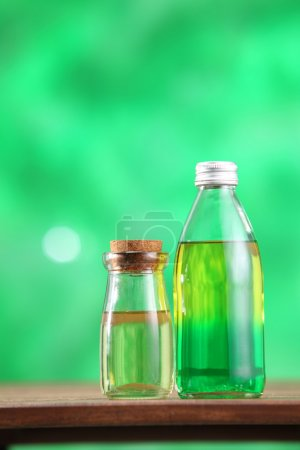Photo for Bottle with massage oil on the green background - Royalty Free Image