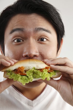 Photo for Man eating burger on the white background - Royalty Free Image