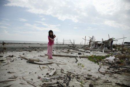 Photo pour Enfant jouant sur la plage polluée - image libre de droit