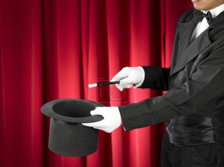 Photo pour Mains du magicien avec baguette magique et chapeau haut de forme sur scène . - image libre de droit