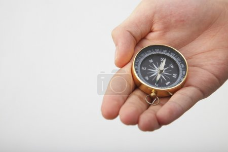 Photo for Hand show a compass on the plain background - Royalty Free Image