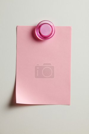 Blank pink note with magnet on the bridge