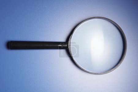 A black magnifying glass with blue background