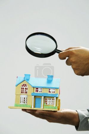 Real estate agent holding a magnifier focus on model house
