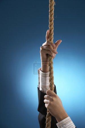 Foto de Un hombre de negocios con traje tirando de la cuerda hacia arriba - Imagen libre de derechos