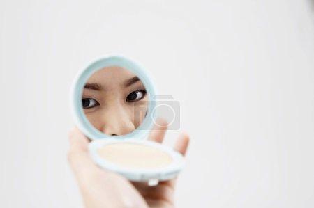 Photo pour Femme regardant dans un miroir compact - image libre de droit