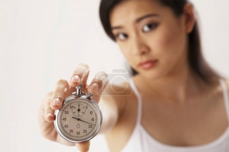Photo for Young woman holding a stop watch - Royalty Free Image