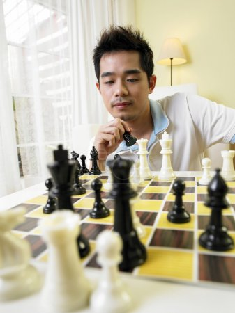Young man moving his chess piece for his next move