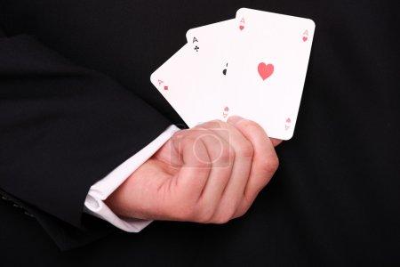 Photo pour Une photo d'une main de jeune entrepreneur tenant trois aces dans le dos - image libre de droit