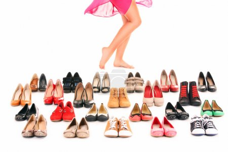 Photo for A picture of sexy female legs among shoes over white background - Royalty Free Image