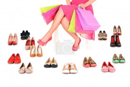 Photo pour Une photo d'une jeune femme assise avec des sacs à provisions parmi les chaussures sur fond blanc - image libre de droit
