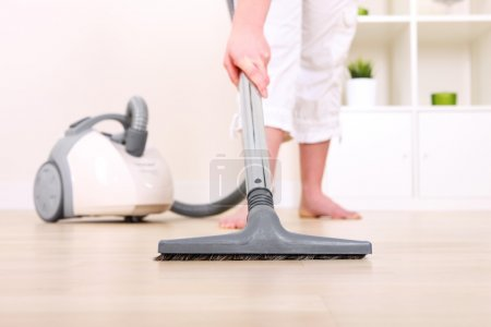 A picture of a young wife hoovering her apartment...