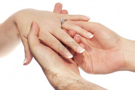 Photo pour Mains masculines plaçant bague de fiançailles en or blanc sur la main des mariées . - image libre de droit