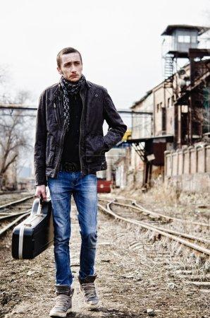 Photo pour Jeune musicien avec étui de guitare à la main va parmi les ruines industrielles - image libre de droit