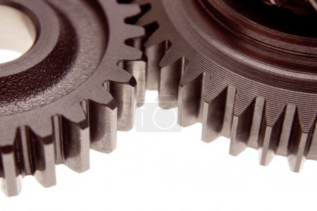 Closeup of two cogs on plain background