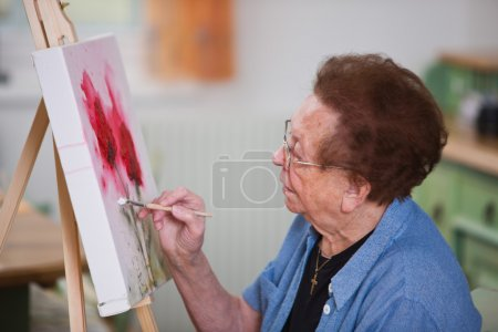 Elderly woman active in leisure time painting a picture