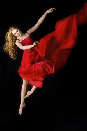 Photo pour Image dramatique d'une femme portant une robe rouge sautant sur un fond noir - image libre de droit