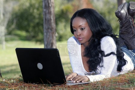 An extraordinarily beautiful young woman dressed in casual wear, works on her laptop computer outdoors.