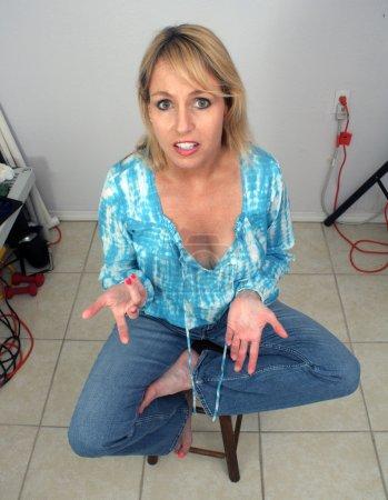 Photo pour Une belle blonde est assise au milieu de l'encombrement à l'intérieur. Point de vue élevé avec légère distorsion grand angle . - image libre de droit