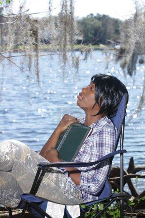 Photo pour Une charmante jeune femme regarde loin de son livre au bord de l'eau . - image libre de droit