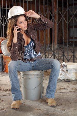 Photo pour Une belle jeune brune, tenant un casque et portant des bottes, parle sur son téléphone cellulaire car elle se situe sur un seau au milieu de l'image de fond d'un entrepôt abandonnée depuis longtemps. - image libre de droit