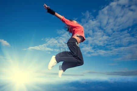 Photo for Beautiful sport woman in urban sportswear jumping and fly over blue sky with clouds and sun beam - Royalty Free Image
