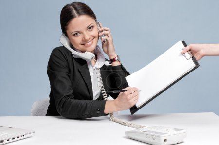 Photo for Busy business woman in office talking by two phones and sign a papers at work place. Smile - Royalty Free Image