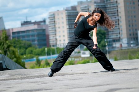Photo for Beautiful teenage girl dancing hip-hop over urban city landscape - Royalty Free Image