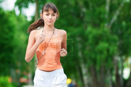 Photo for Beautiful teenage girl running in green park on sunny summer day - Royalty Free Image