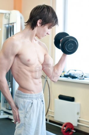 Powerful muscular man lifting weights in gym