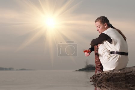Lonely woman sitting on lake coast