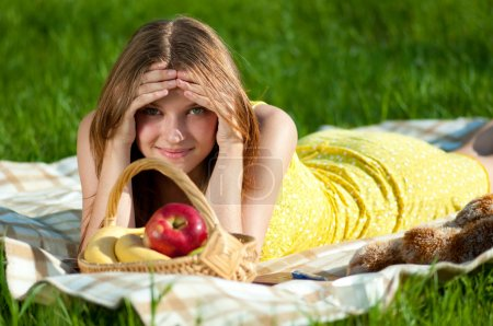 Beautiful young woman on picnic with fruits