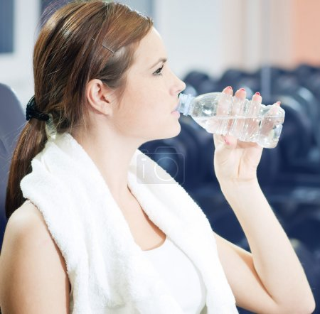 Beautiful sport woman drink water at gym