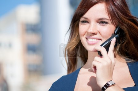 Photo for Young business woman using mobile cell phone over city background. Student - Royalty Free Image